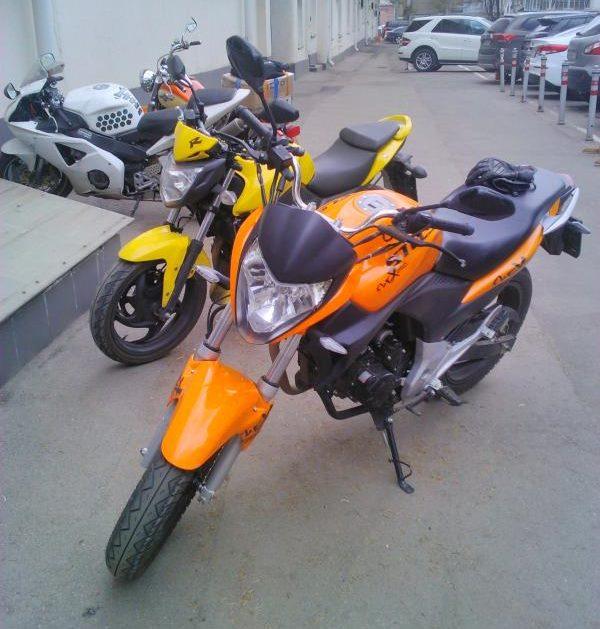 Два байка оранжевой и желтой расцветок модели Stels FLEX 250 рядом с автостоянкой