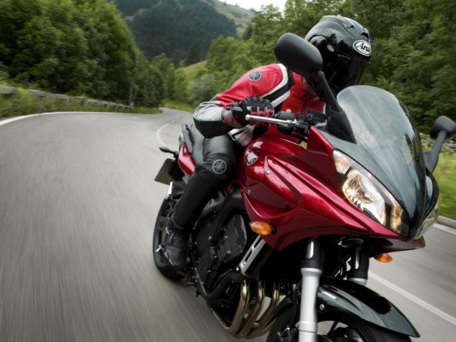 Мотоциклист в черном шлеме мотоцикле Yamaha FZ6 Fazer с обтекателем малинового цвета
